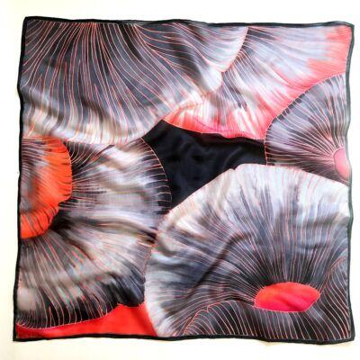 A kalap alatt narancs-szürke nagy selyemkendő